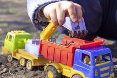 Ребенок играет в улице с песком; он нагружает землю в игрушке самосвал стоковое фото