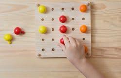 Ребенок играет с деревянными красочными шариками Игра для детей Стоковое Изображение