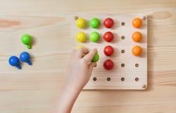 Ребенок играет с деревянными красочными шариками Игра для детей Стоковые Изображения