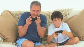 Ребенок играя видеоигры с его дедом видеоматериал