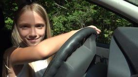 Ребенок играя в вождении автомобиля претендует, ягнится приключение в автомобиле, наслаждаться девушки сток-видео