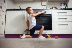 Ребенок играя в кухне с газовой плитой Стоковые Изображения