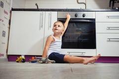 Ребенок играя в кухне с газовой плитой Стоковые Фотографии RF