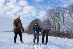 Ребенок играя в снеге с мамой Стоковые Изображения