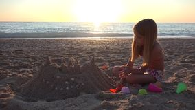 Ребенок играя замок песка на пляже на заходе солнца, девушке на Seashore, береговой линии 4K сток-видео