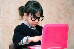 Ребенок играя за розовой компьтер-книжкой Стоковое Изображение RF