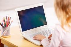 Ребенок играя игру на компьтер-книжке Стоковые Изображения RF