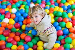 Ребенок играя на красочной пластичной спортивной площадке шариков Стоковое фото RF