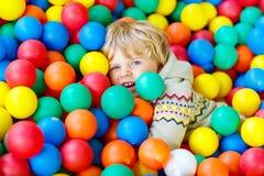 Ребенок играя на красочной пластичной спортивной площадке шариков Стоковая Фотография RF