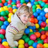 Ребенок играя на красочной пластичной спортивной площадке шариков Стоковые Изображения