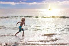Ребенок играя на пляже океана Ребенк на море захода солнца стоковые фотографии rf