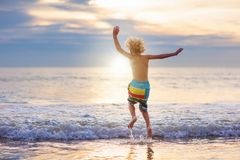 Ребенок играя на пляже океана Ребенк на море захода солнца стоковые изображения rf