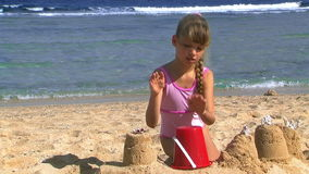 Ребенок играя на sandcastles пляжа и строения акции видеоматериалы