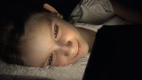 Ребенок играя планшет в темной ночи, интернет просматривать девушки в кровати, не спать сток-видео