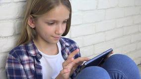 Ребенок играя планшет, смартфон ребенк, сообщения чтения девушки просматривая интернет сток-видео