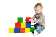 Ребенок играя при кубики игрушки, изолированные на белизне стоковые изображения