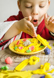Ребенок играя при тарелка спагетти сделанная с пластилином Стоковое Изображение RF