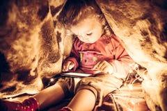 Ребенок играя при умный телефон пряча в секретном месте под одеялом от родителей Стоковая Фотография