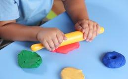 Ребенок играя с глиной моделирования Стоковое Изображение RF