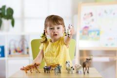 Ребенок играя с игрушками животного на таблице Стоковые Фотографии RF