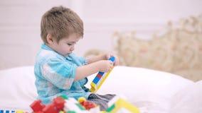 Ребенок играя с красочными блоками игрушки Игра детей Башня здания мальчика игрушек блока сидя на кровати в белизне акции видеоматериалы