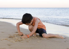 Ребенок играя с песком на пляже стоковые изображения rf
