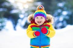 Ребенок играя с снегом в зиме малыши outdoors стоковые изображения