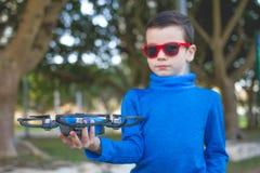 Ребенок играя с трутнем outdoors на летнем дне Стоковая Фотография