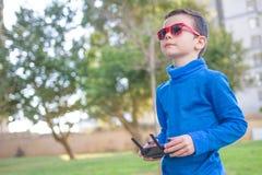 Ребенок играя с трутнем outdoors на летнем дне Стоковое Изображение