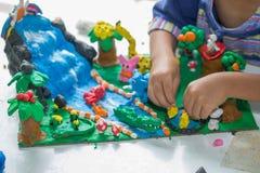 Ребенок играя с формами прессформы глины, творческие способности детей стоковая фотография