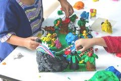 Ребенок играя с формами прессформы глины, творческие способности детей стоковые фото