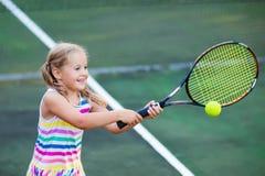 Ребенок играя теннис на внешнем суде Стоковое Изображение RF