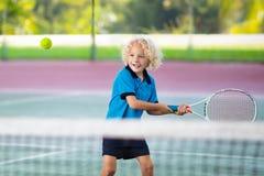 Ребенок играя теннис на внешнем суде стоковая фотография rf