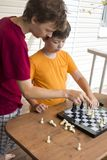 Ребенок играя outdors шахмат, молодой мальчика делая движение Стоковые Изображения RF