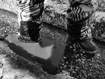 Ребенок идет в ботинки через лужицы весной или зиму в солнечной погоде стоковые изображения rf