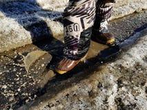 Ребенок идет в ботинки через лужицы весной или зиму в солнечной погоде стоковое изображение rf