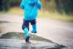 Ребенок идя в wellies в лужице на ненастной погоде Стоковое Изображение RF
