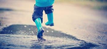 Ребенок идя в wellies в лужице на ненастной погоде Стоковое Фото