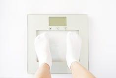 Ребенок измеряет вес на масштабах Стоковое Изображение RF