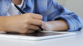 Ребенок изучая на планшете, сочинительстве девушки в школьном классе, уча делающ домашнюю работу видеоматериал