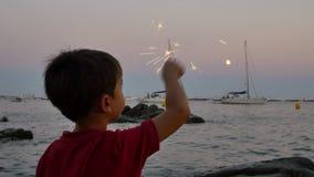 Ребенок имея потеху со сверкная пирофакелом на заходе солнца видеоматериал