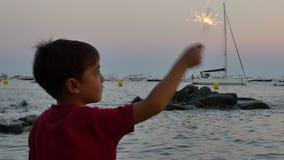 Ребенок имея потеху со сверкная пирофакелом на заходе солнца акции видеоматериалы