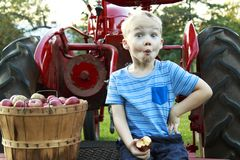 Ребенок имея рудоразборку и усаживание яблока потехи на красном античном trac Стоковые Изображения