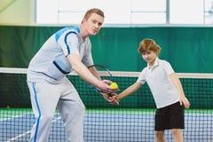 Ребенок инструктора или тренера уча как сыграть теннис на суде крытом стоковые фото