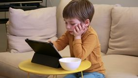 Ребенок используя ПК планшета на кровати дома Милый мальчик на софе наблюдает мультфильм, играет игры и учит от ноутбука Образова акции видеоматериалы