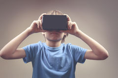 Ребенок используя новую 3D виртуальную реальность, стекла картона VR Стоковое Фото