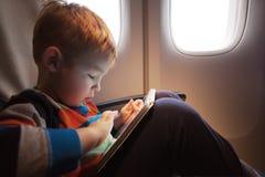Ребенок используя планшет во время полета стоковое изображение rf