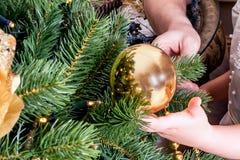 Ребенок и взрослый украшают рождественскую елку стоковая фотография
