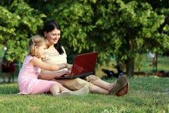 Ребенок и девушка с компьтер-книжкой Стоковая Фотография