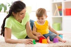 Ребенок и его мать играя вместе с игрушками стоковое фото